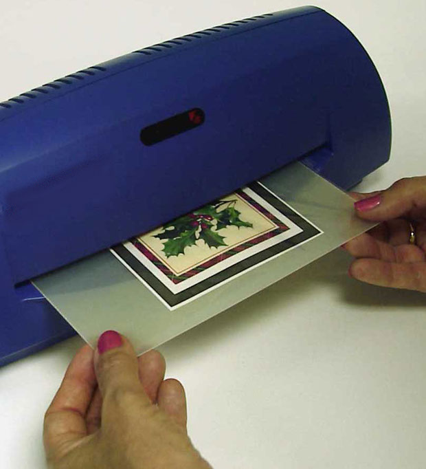 "Photo: Applying ""ClearCoat"" foil over printed greeting card, being inserted into laminator & reinserting with Mylar Carrier"